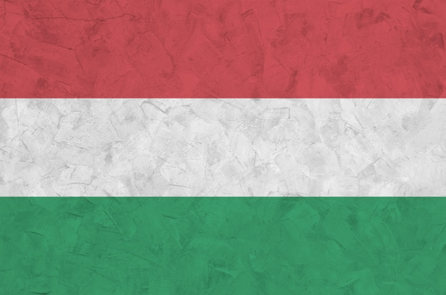 Hungary flag depicted in bright paint colors on old relief plastering wall.