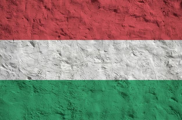 古い救済左官壁に明るいペンキ色で描かれたハンガリーの国旗。大まかな背景に織り目加工のバナー