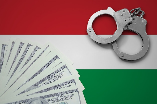 Hungary flag  with handcuffs and a bundle of dollars. the concept of illegal banking operations in us currency