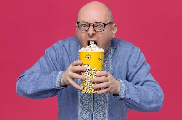 Голодный взрослый славянский мужчина в синей рубашке в оптических очках держит ведро с попкорном