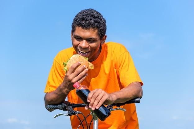 배고픈 아프리카계 미국인 남자는 여름에 야외에서 자전거에 앉아 햄버거와 콜라 음료의 맛을 즐기고 있습니다. 정크 푸드 다이어트에 대한 사랑의 개념