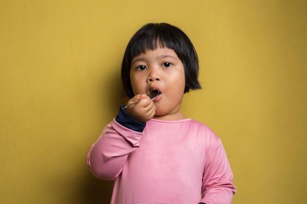 黄色の壁にスプーンを持っている空腹のアジアの女の子