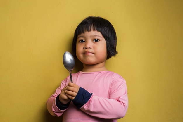 Hungry asian girl holding a spoon on yellow wall