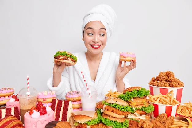 Hungry asian lady looks gladfully at a doughnut surrounded by fast food