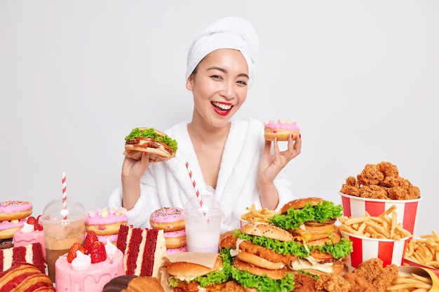 Hungry asian lady smiles gladfully holds doughnut and sandwich surrounded by fast food