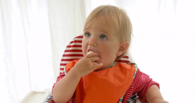 Hungry baby girl eating a banana.