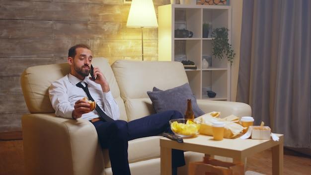 ハンバーガーを食べながら携帯電話で会話をしている空腹のビジネスマン。テーブルの上のビール。