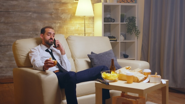 Uomo d'affari affamato che conversa sul cellulare mentre mangia un hamburger. birra in tavola.