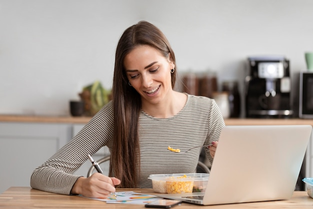 Hungry businesswoman eating and homeworking