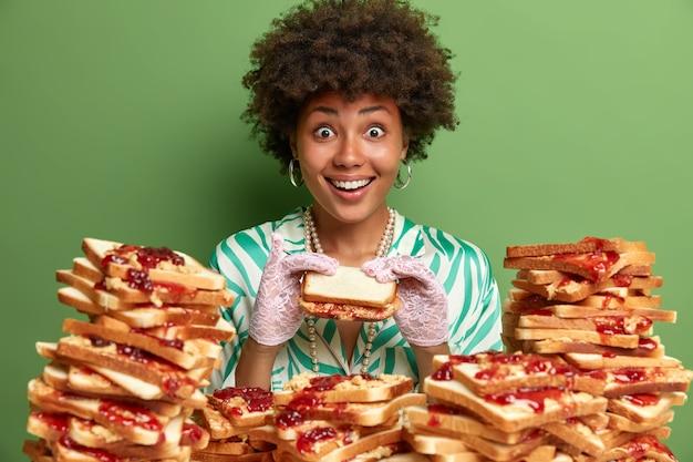 La donna allegra affamata mangia uno spuntino delizioso, ha un aspetto positivo, ha buon appetito e gola, indossa un vestito elegante e guanti, posa vicino a molti toast di pane, isolato sul muro verde