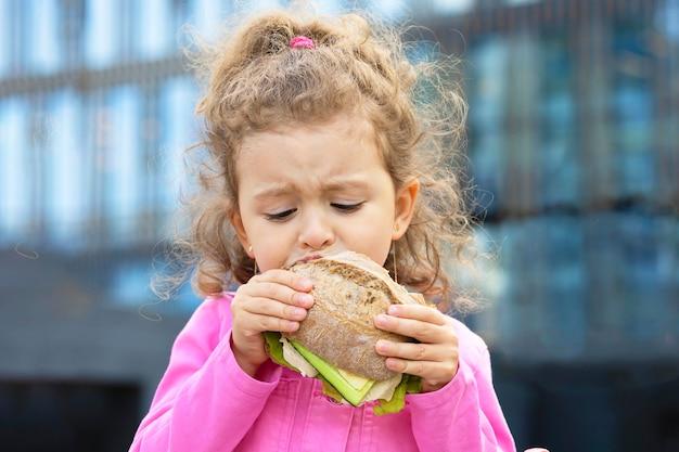 배고픈 아이의 식욕은 패스트 푸드를 먹습니다. 여자 물린 집에서 샌드위치. 학교에서 건강에 해로운 건강한 식사