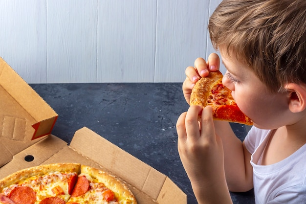 Hungry child eats pizza pepperoni appetite at home. close up. italian traditional lunch or dinner. children's snack