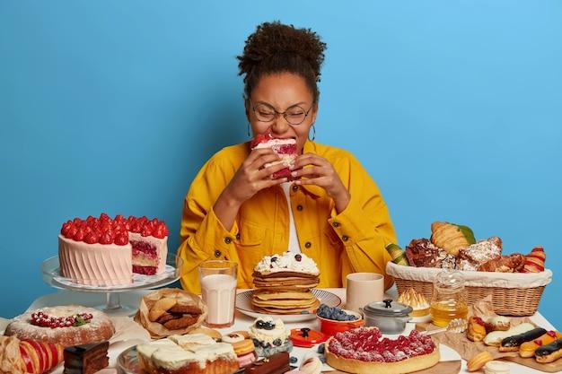 배고픈 곱슬 곱슬 한 여자가 식욕을 돋우는 크림 딸기 케이크로 먹고, 설탕 중독이 있고, brithday에 와서, 다양한 디저트를 맛 봅니다.