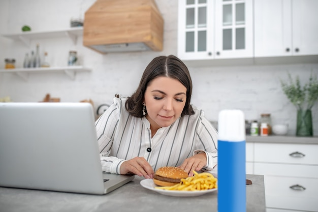 Hungry. dark-haired woman in a striped blouse looking at the plate with food