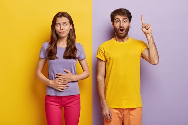Голодная темноволосая женщина трогает живот, хочет съесть что-нибудь вкусненькое, носит фиолетовую футболку и розовые брюки
