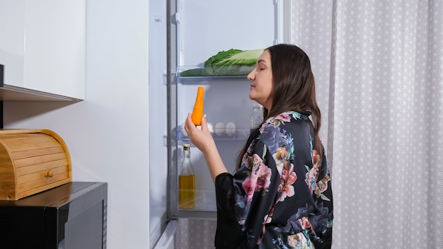 Hungry dieting young woman in dark gown with floral print opens door of modern fridge to take sweet cake in kitchen at night close view