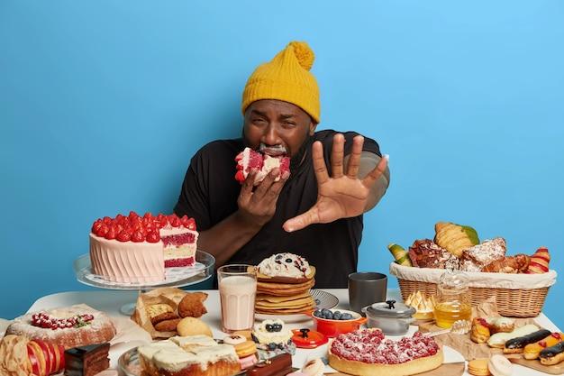 L'uomo afro paffuto e dispiaciuto affamato tiene il palmo davanti alla telecamera, morde un enorme pezzo di torta cremosa, riceve molte calorie, circondato da gustosi prodotti da forno
