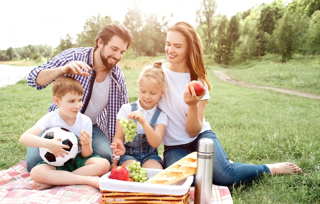 Hungry family is sitting on blanket and looking at basket with food. woman has apple in her hands. girl is holding grapes in hands. boy is eating a piece of grape. man wants to grab food from basket