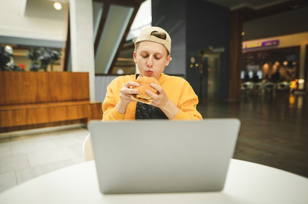 Hungry freelancer eats a burger in a fast-food restaurant
