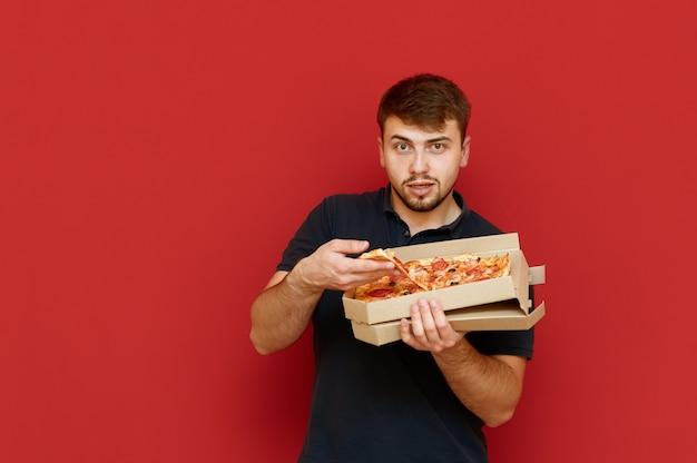 배고픈 재미있는 사람이 서서 상자에서 피자 조각을 꺼냅니다.