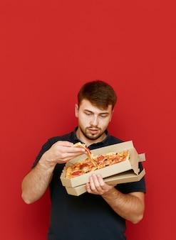空腹の面白い男が立って、箱からピザのスライスを取り出します