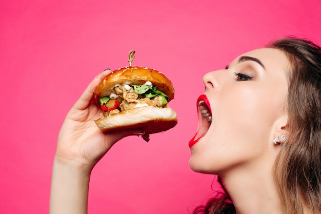 Hungry girl with opened mouth eating big hamburger.