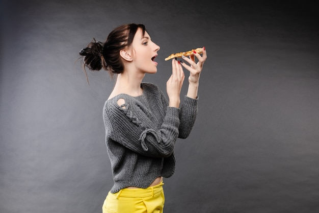 Hungry girl with opened mouth eating pizza