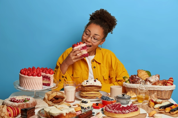 Hungry greedy afro american girl bites big delicious piece of cake, poses at table with many yummy desserts, has sweet breakfast at home, unhealthy nutrition, isolated over blue wall