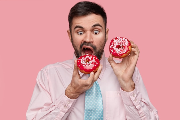 Hungry handsome man bites red doughnut, wears formal shirt with tie, opens mouth widely
