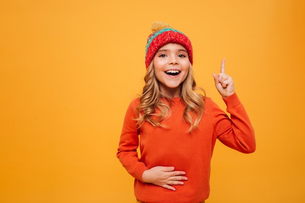 Hungry happy young girl in sweater and hat holding her tummy and having idea while looking at the camera over orange