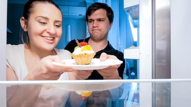 空腹の夫と妻は、キッチンで深夜に最後のケーキを求めて戦っています。ダイエットと健康的な栄養の概念。