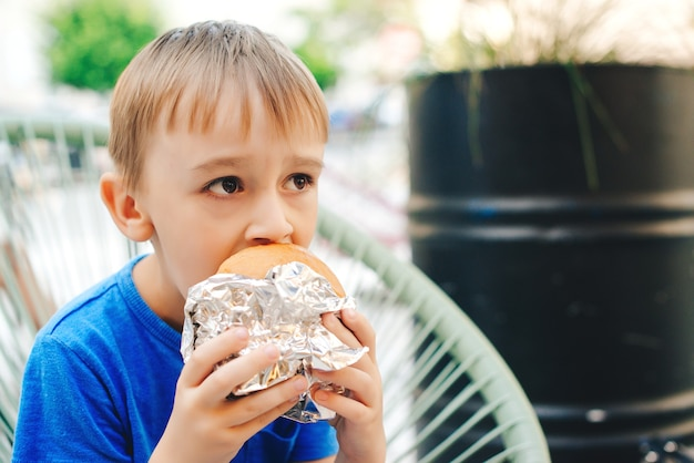 Hungry kid eating a burger at outdoors cafe.