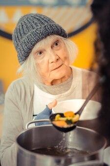 空腹の生活。ボランティアセンターに来てスープを求めて悲しい陽気な女性