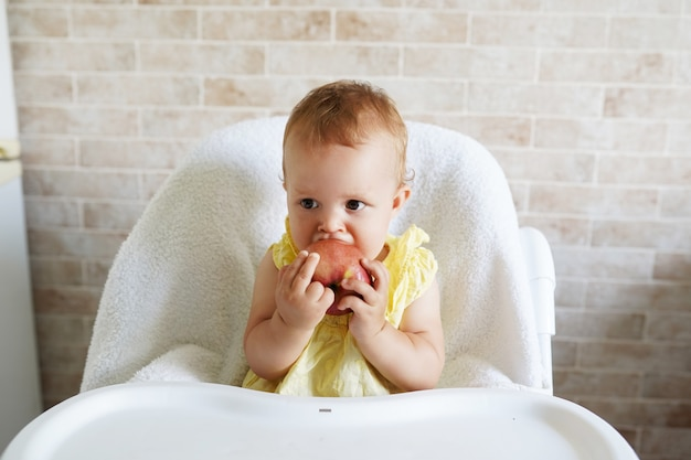 Hungry little baby girl eating apple