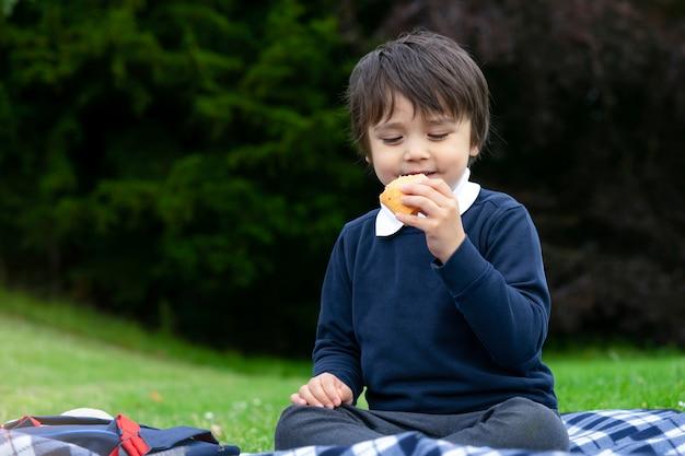 新鮮なトルティーヤを食べる空腹の小さな男の子は鶏肉、ベーコン、混合野菜でラップ、公園でピクニックをしているかわいい学校の少年、夕食にメキシコのサンドイッチ料理を食べる子供