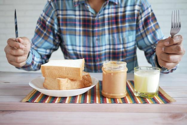 Голодный человек ест хлеб с арахисовым маслом и молоко на столе
