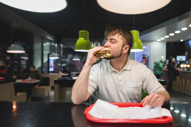 Голодный человек ест большой аппетитный гамбургер за столом в ресторане быстрого питания. концепция быстрого питания