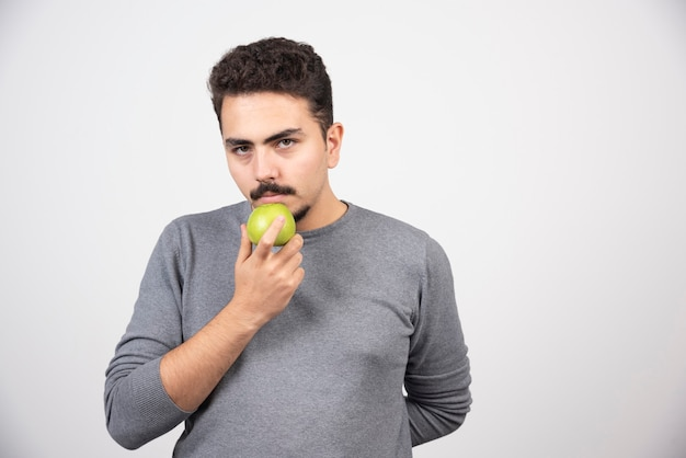 Uomo affamato che tiene mela verde e che sembra serio.