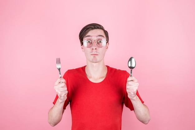 배고픈 남자는 손에 포크와 숟가락을 들고 맛있는 음식에 대해 생각합니다.