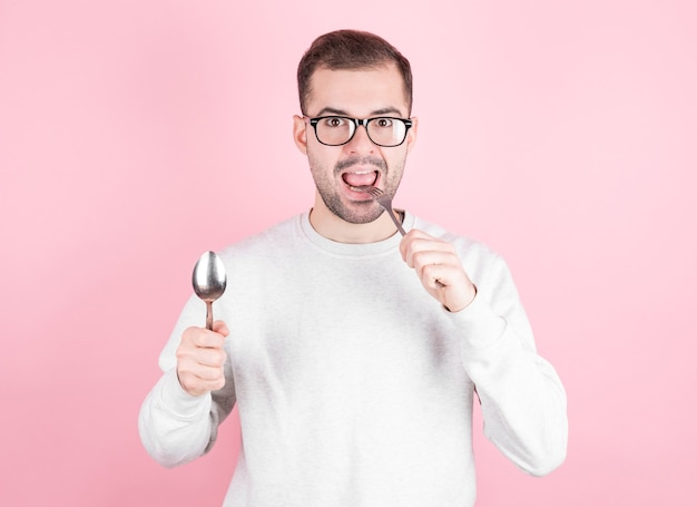 배고픈 남자는 포크와 숟가락을 손에 들고 입술을 핥는 다. 다이어트, 음식 섭취 및 배고픔의 개념.