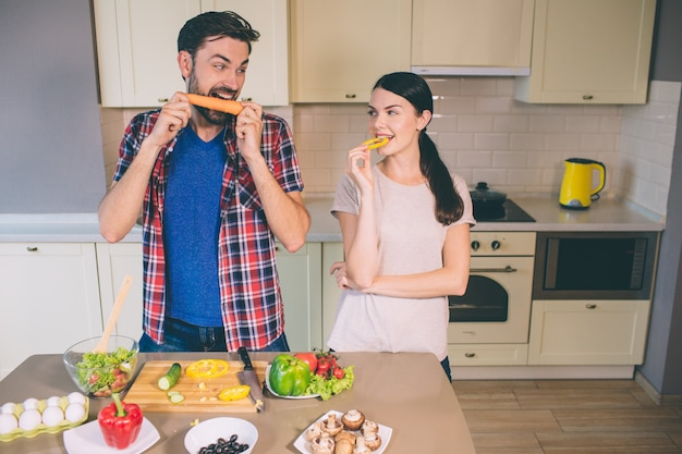 Hungry man stands and looks at girl. he devours carrot. girl looks at vegetable.