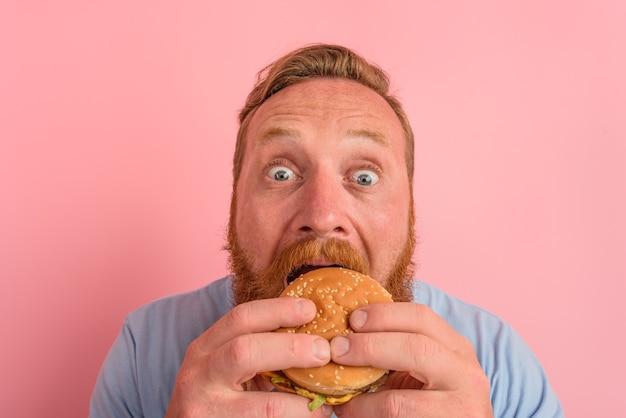 수염과 문신을 한 배고픈 남자는 햄버거와 함께 샌드위치를 먹는다
