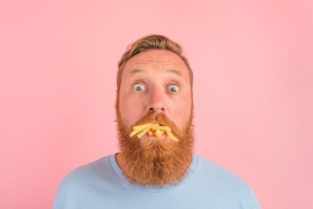 수염과 문신을 한 배고픈 남자는 짭짤한 튀긴 감자를 먹는다