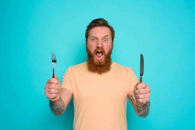 귀영 나팔을 가진 배고픈 남자는 손에 칼 붙이로 먹을 준비가되었습니다.