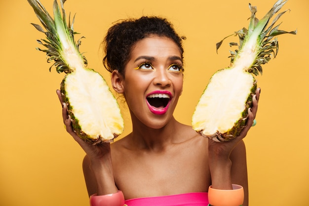 Hungry mulatto woman with colorful makeup looking upward and holding two parts of fresh appetizing pineapple isolated, over yellow wall