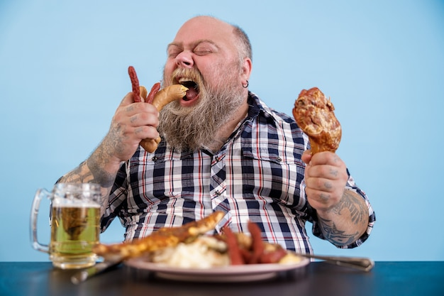 Hungry plus size man eats sausages at table with rich food and mug of beer