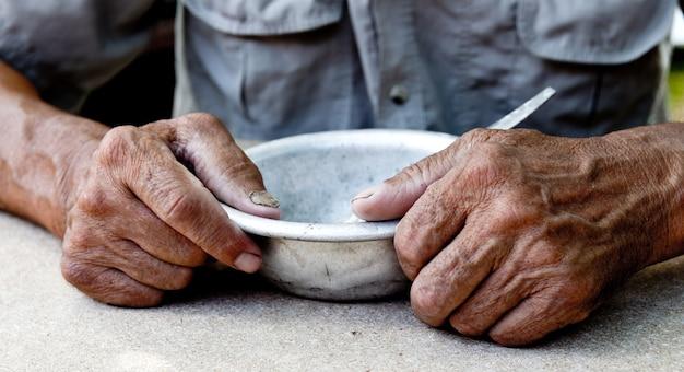 空腹の貧しい老人の手は空のボウル