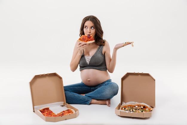 Голодная беременная женщина ест пиццу.
