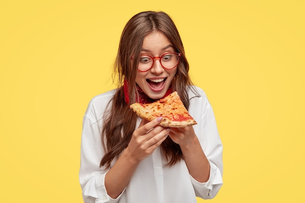 Голодный студент широко открывает рот, видит вкусный кусок пиццы, хочет съесть, одетый в белую рубашку, модели у желтой стены. положительная женщина с нездоровой пищей. люди и еда