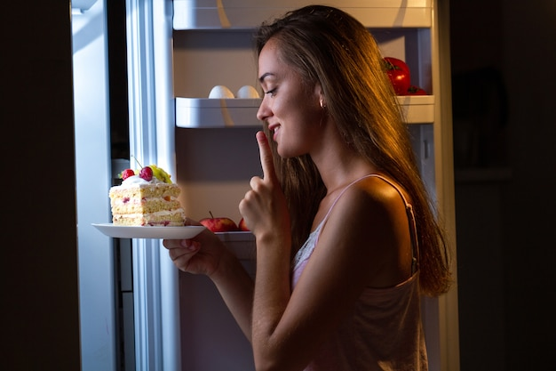 Голодная женщина в пижаме ест сладкий торт ночью возле холодильника. прекратите диету и наберите лишние килограммы из-за вредной пищи с высоким содержанием углеводов и нездоровой пищи